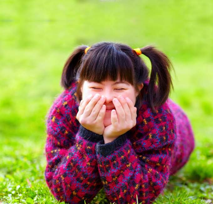 Happy young girl with disability relaxing on spring lawn