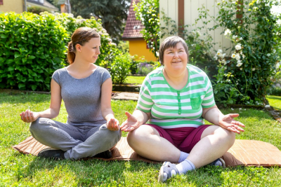 yoga coach and mentally disabled woman doing some yoga or relaxation exercises